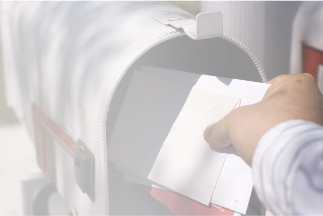man taking mail out of mailbox